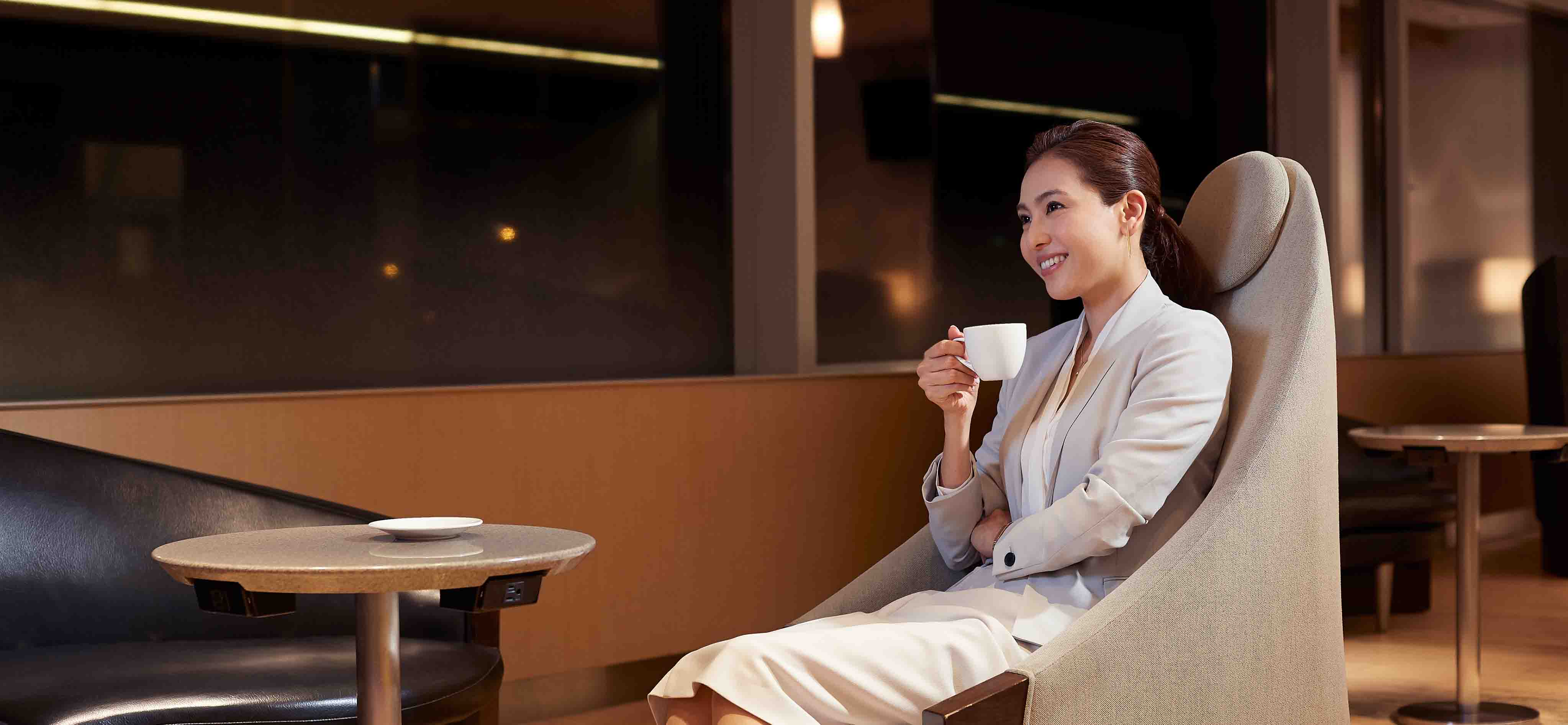 A woman drinking coffee at lounge